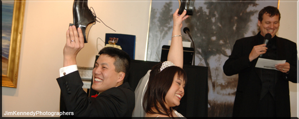 Idea Credits for The Best Wedding Reception Ever! Bride & Groom holding up shoes while answering newlywed quiz questions being posed by their Wedding Entertainment Director, Peter Merry.